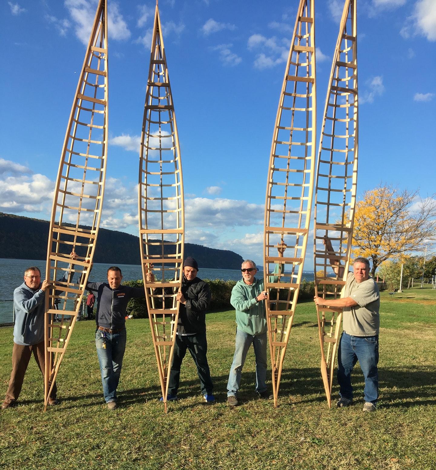 Four men holding kayak frames while building boats