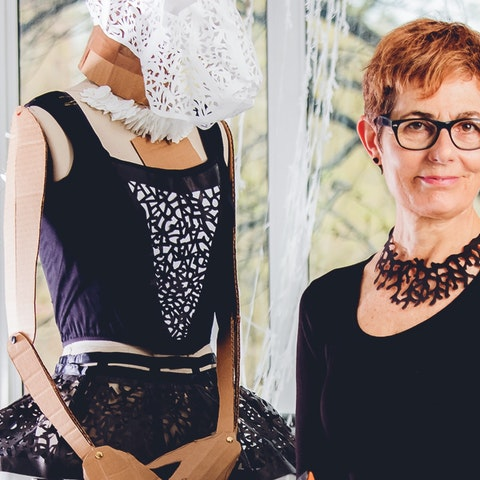 Visual artist Beatrice Coron posing with and wearing her cut creations. Photo by Ric Kallaher.