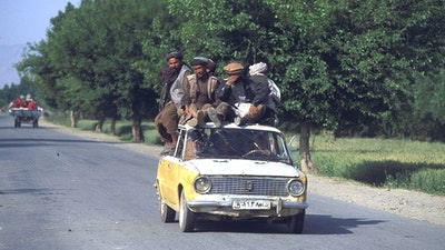 """Men sit on the roof of a taxi to Kunduz."""