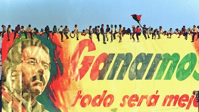 """Supporters of Daniel Ortega sit on a billboard reading: 'We win and everything will be better' in Managua, Nicaragua, 1990."""