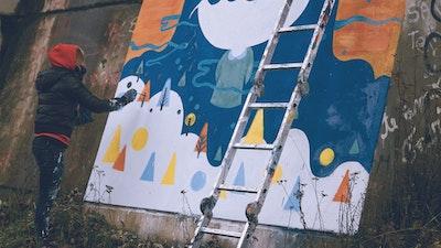 Street artist at work: Pum Pum working on a winter themed wall mural in Buenos Aires via Vacation with an Artist  #creativevacations #vawaa #streetart #urbanart #buenosaires #slowtravel #wallmurals #creativity #argentina